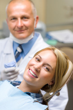A woman smiling with her dentist behind her also smiling