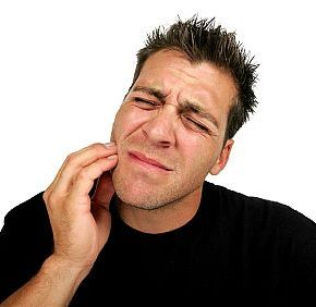 man holding his jaw in need of an emergency dentist