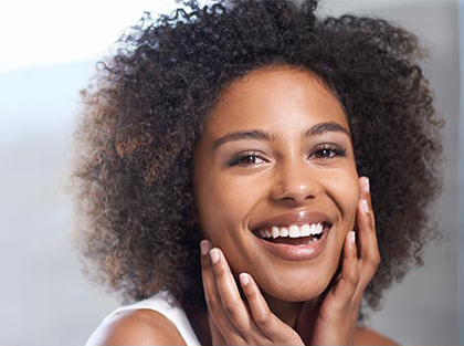 African American woman smiling, for information on facial aesthetics from Dr. Cha in Tulsa